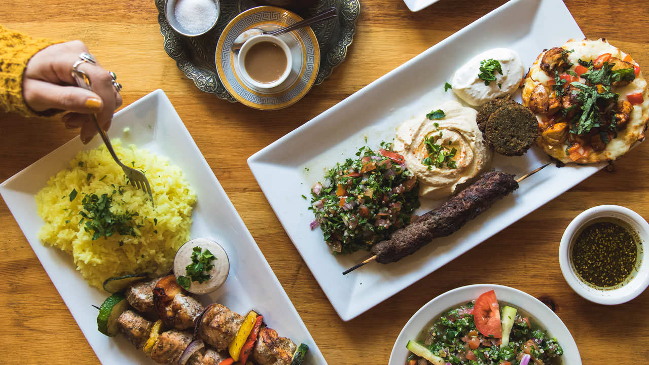 A girl's hand forks yellow rice, one of three delicious Lebanese platters at Nicholas Restaurant.