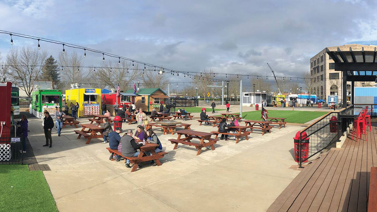 Color food carts line an outdoor space filled with tables, turf and an entertainment space.
