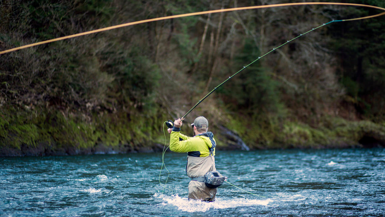 A man fly fishes on a river in Oregon.