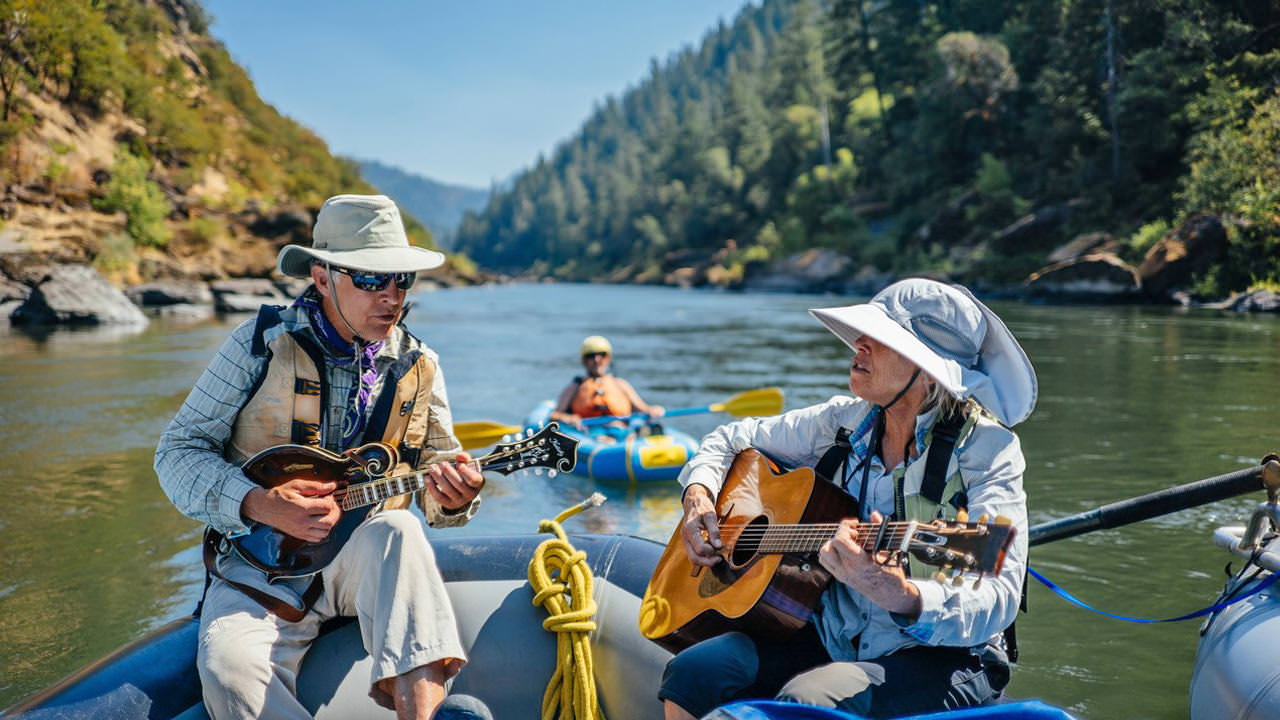 A man and woman wearing breathable fabrics play guitar on a raft down the Rogue River.