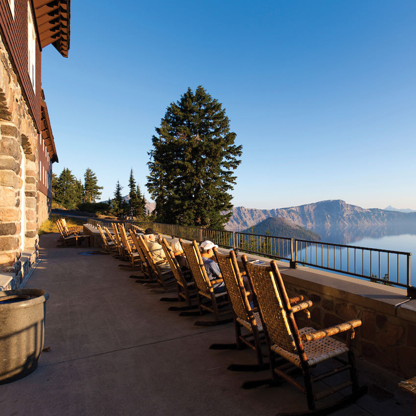 Wicker rocking chairs line a patio overlooking Crater Lake