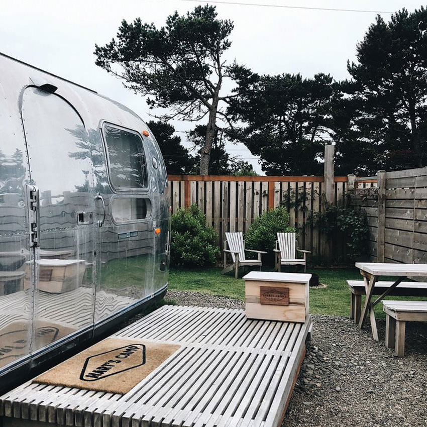 The exterior of an airstream trailer with a wooden deck, chairs and picnic tables in the yard