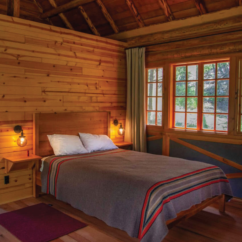 Interior of a cabin with upscale lighting and bedding