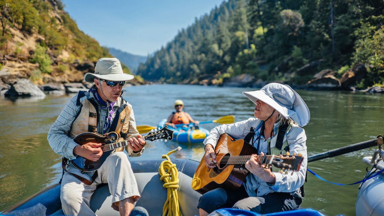 A couple play guitars while floating on a raft down the Rogue River