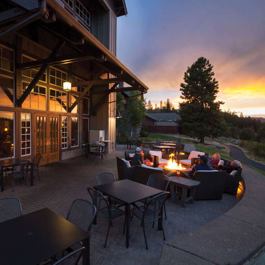 People gather around an outdoor fireplace at sunset