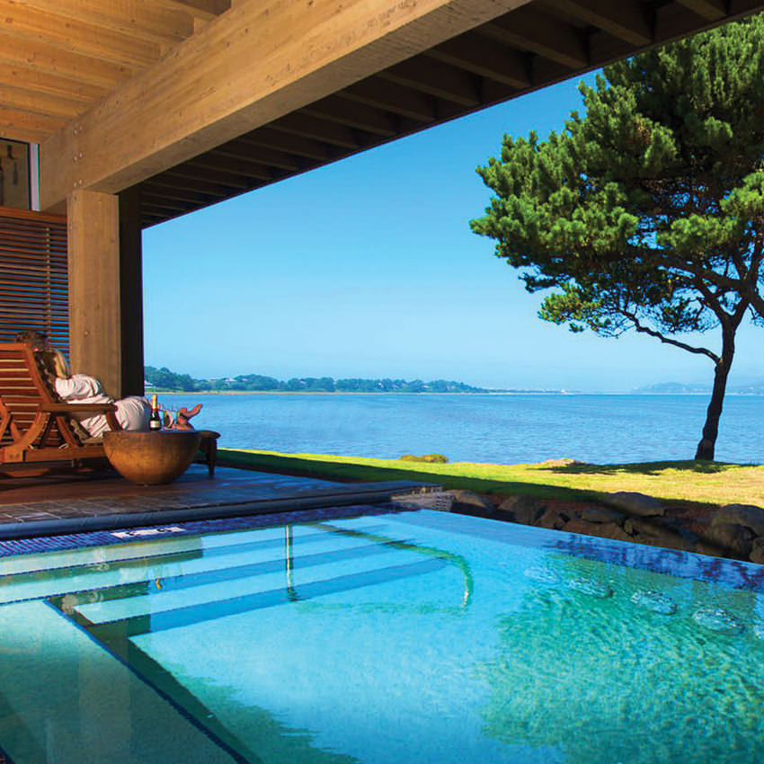 A person lounging next to a covered pool overlooking a bay