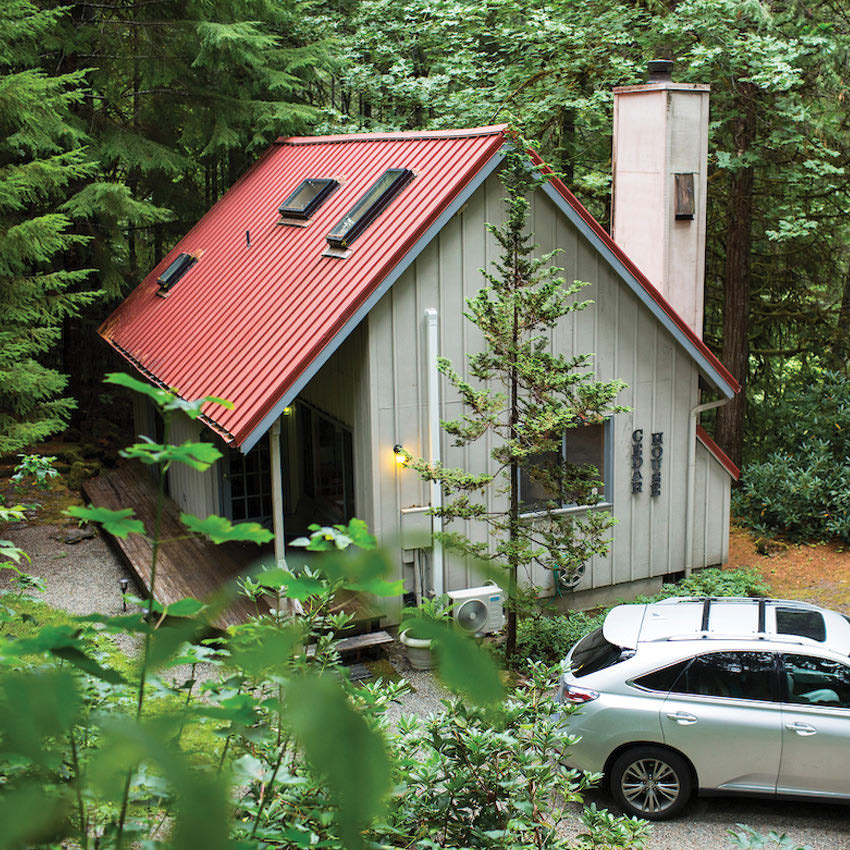 A car parked next to a cabin in the forest
