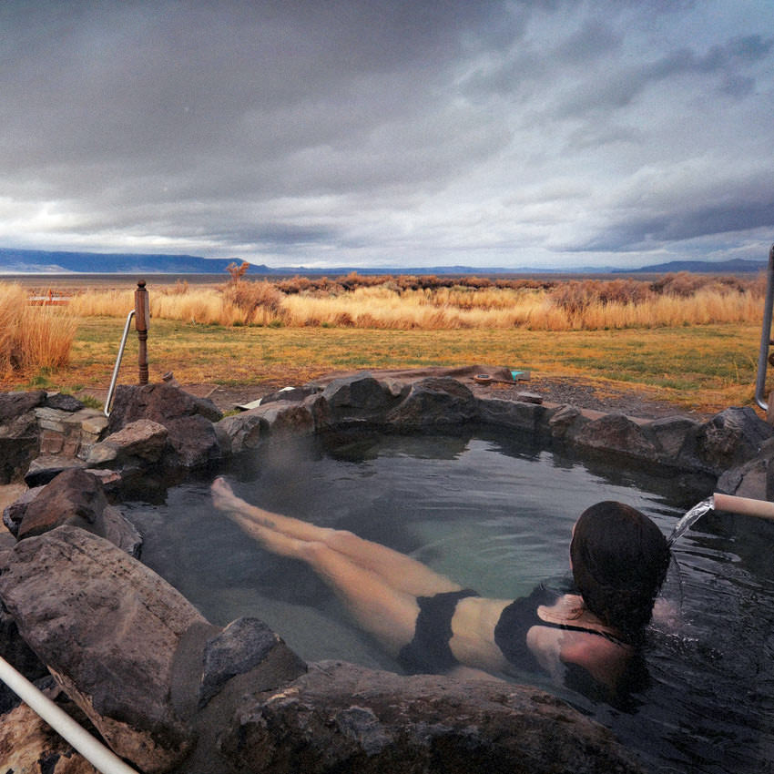 A woman soaks in an outdoor natural hot spring overlooking a prairie