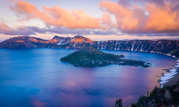 A pink sunset turns Crater Lake National Park into a dreamy scene.