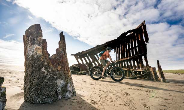 A fat-tire cyclists pedals past a shipwreck on the beach.