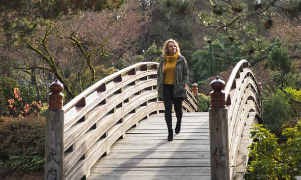 A woman walks on a wooden bridge.