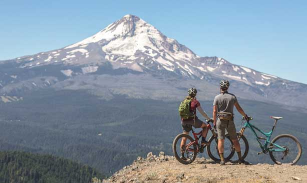 Two cyclists look at Mt. Hood.