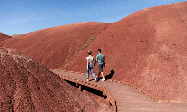 Two people walk on a wooden boardwalk through the bright red Painted Hills.