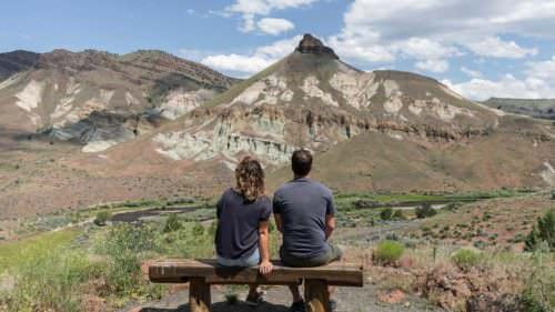 Two people sit on a bench overlooking ancient rock formations.