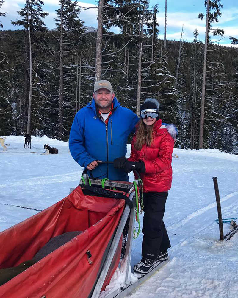 Justin and Grace pose while holding onto the red sled.