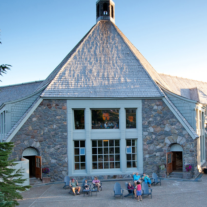 People gather in adirondack chairs in front of the stone lodge's two story windows