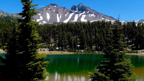 Snow melts on a mountain and its reflection is seen in the green lake.