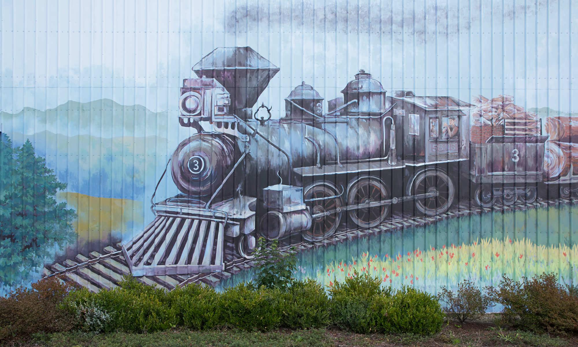 A mural paiting shows a steam engine train riding through agricultural land.