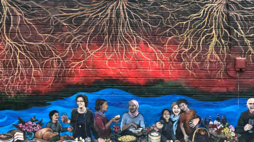 A mural on the Abbey Creek Winery building depicts an array of neighbors interacting and enjoying a large bounty.
