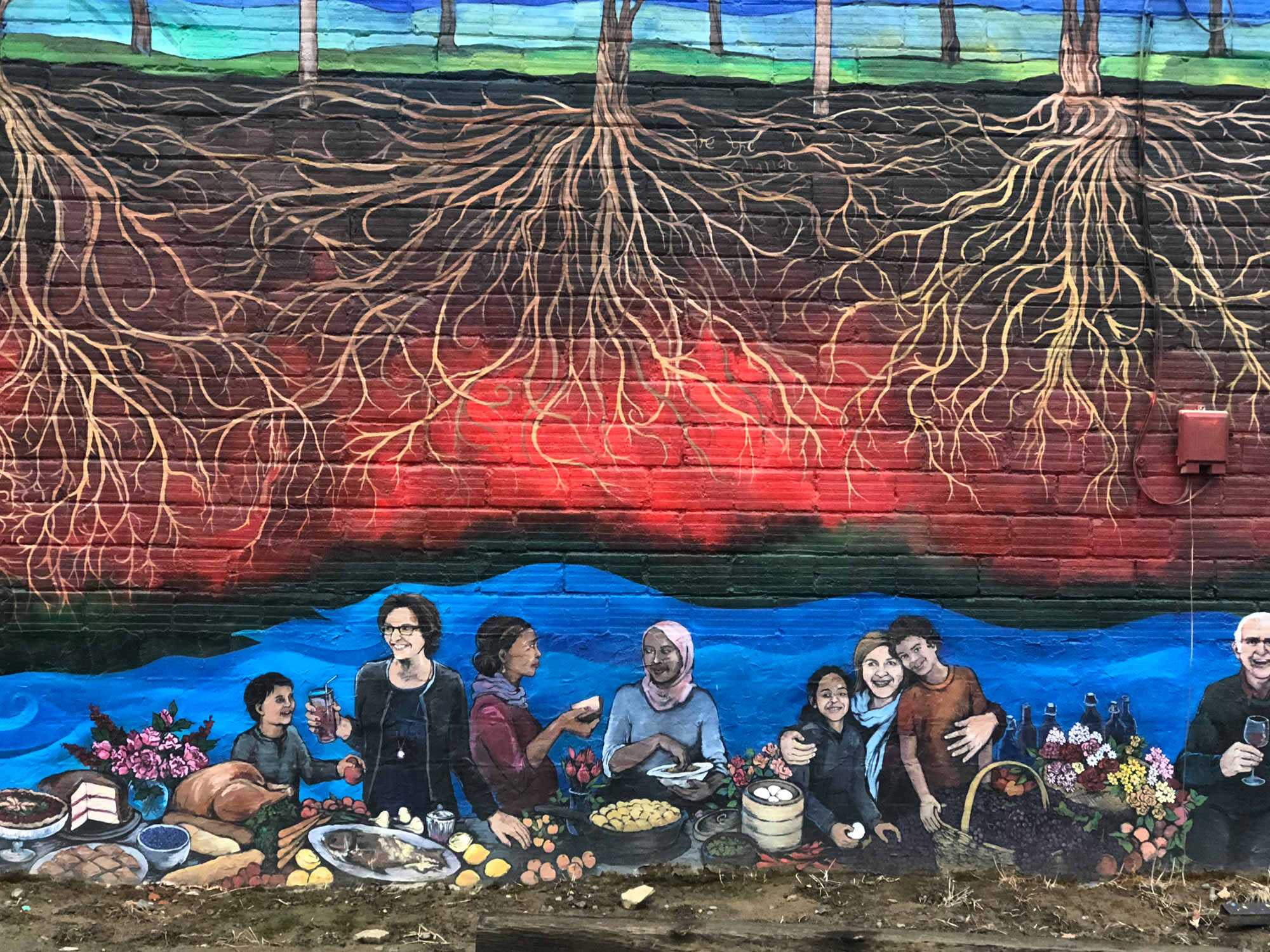 A painting depicts friends gathering over food, artistically under the roots of trees.
