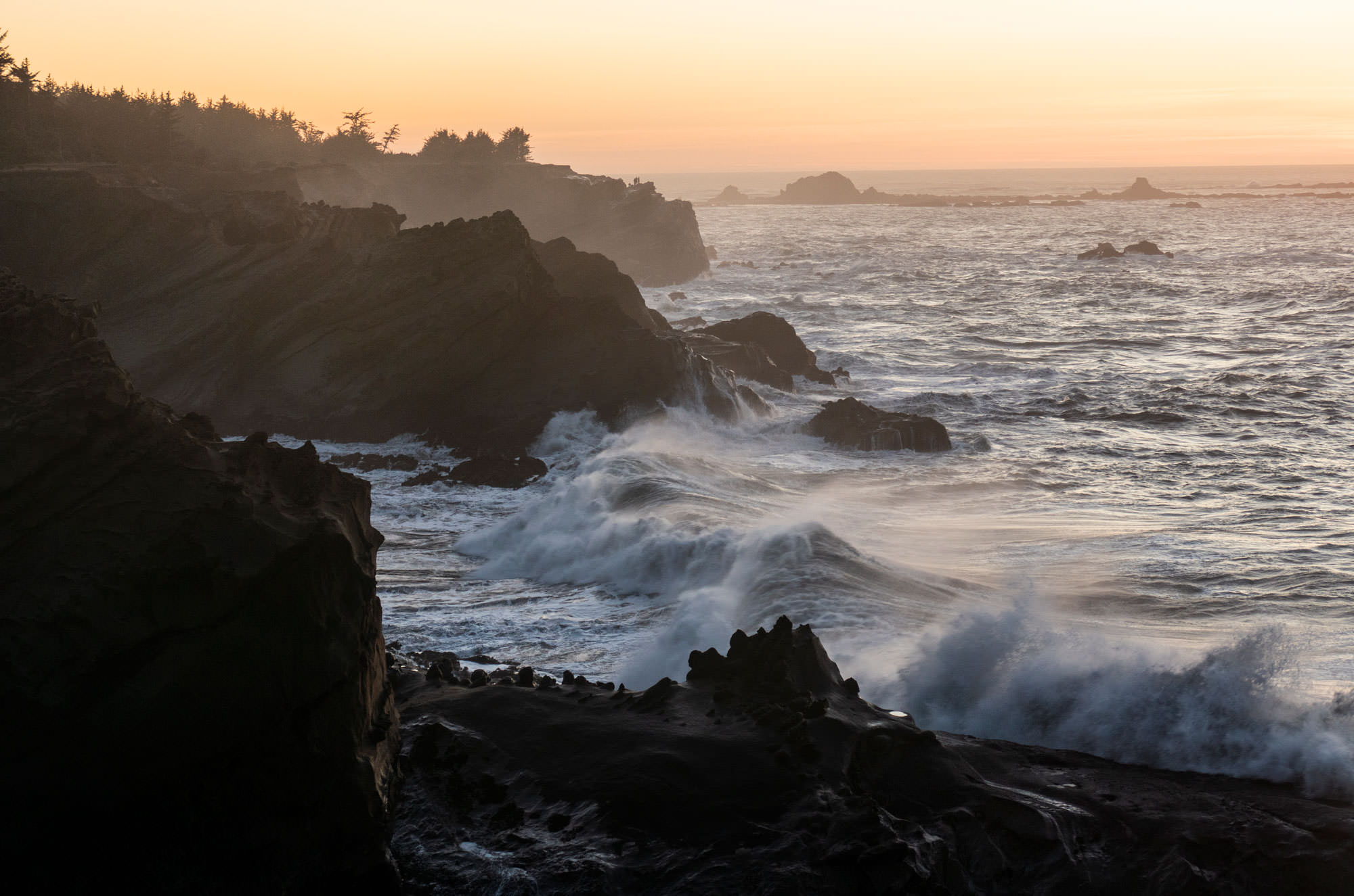 Sunset falls along the Oregon Coast horizon as waves roll towards the shoreline.