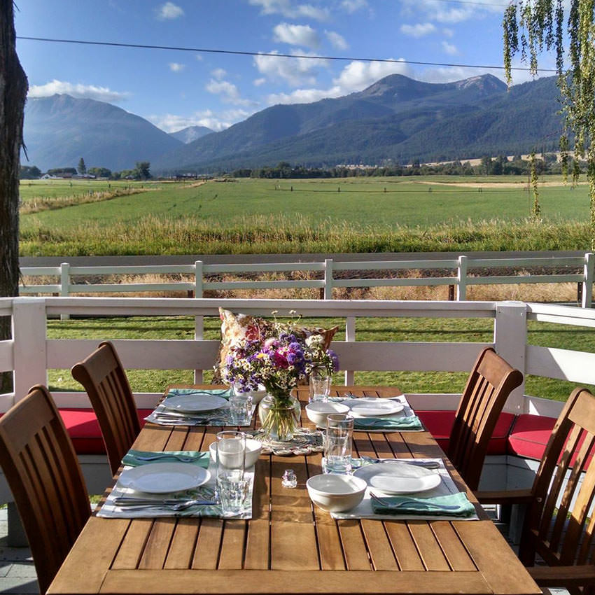 An outdoor table set for four people with a view of mountains