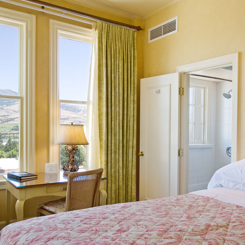 Interior of a brightly lit hotel room with a view of hills out a window