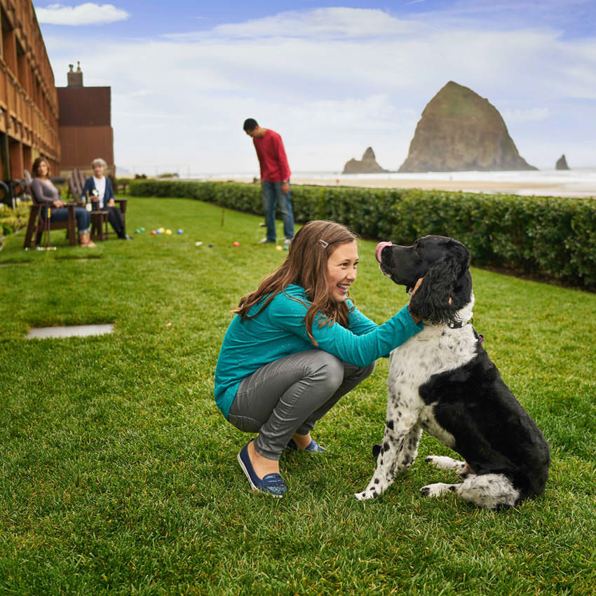 A girl pets her dog on a hotel's grassy lawn above the beach