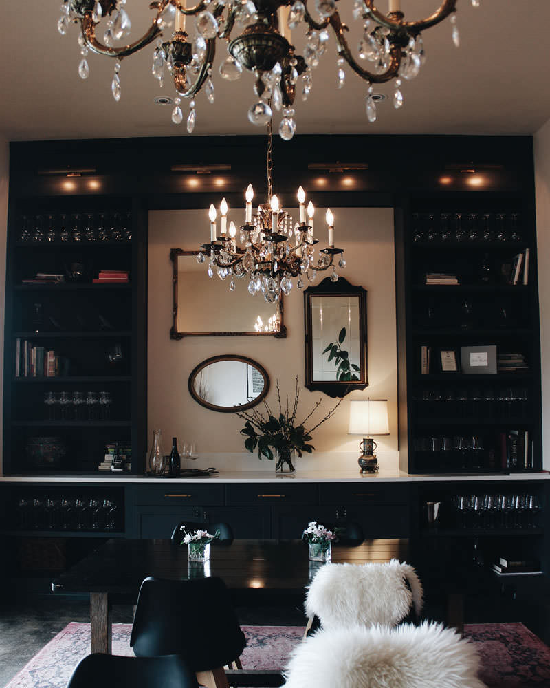 A chandelier hangs above fur-lined chairs and elegant decor.