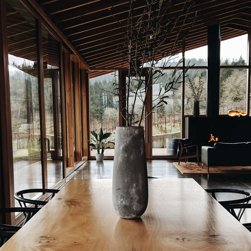 Floor-to-ceiling glass windows surround the tasting room as a fireplace warms up guests inside.