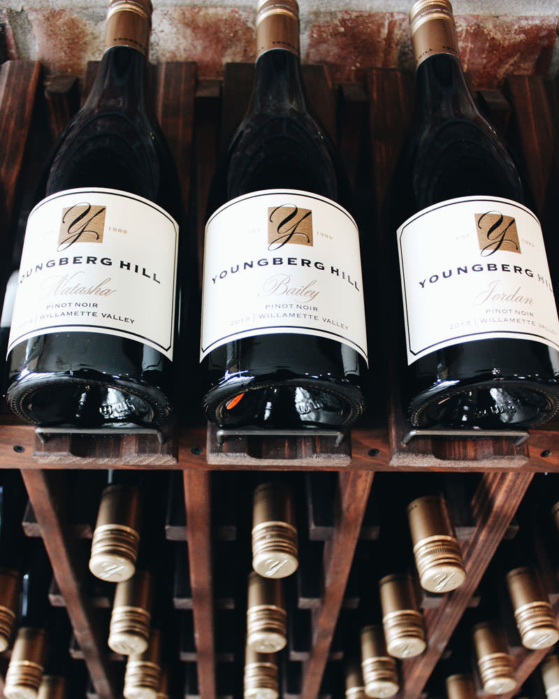 Bottles of Youngberg Hill pinot noir stack on an impressive wine rack.