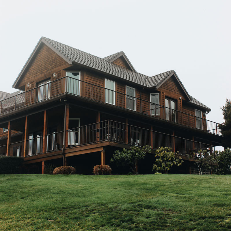 A stunning wooden inn overlooks lush green grass and grape vines.