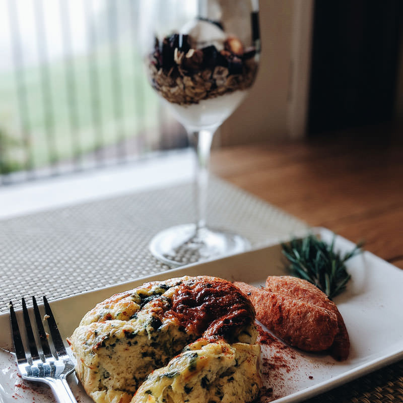 A breakfast quiche and glass of yogurt and granola overlook the vineyard.