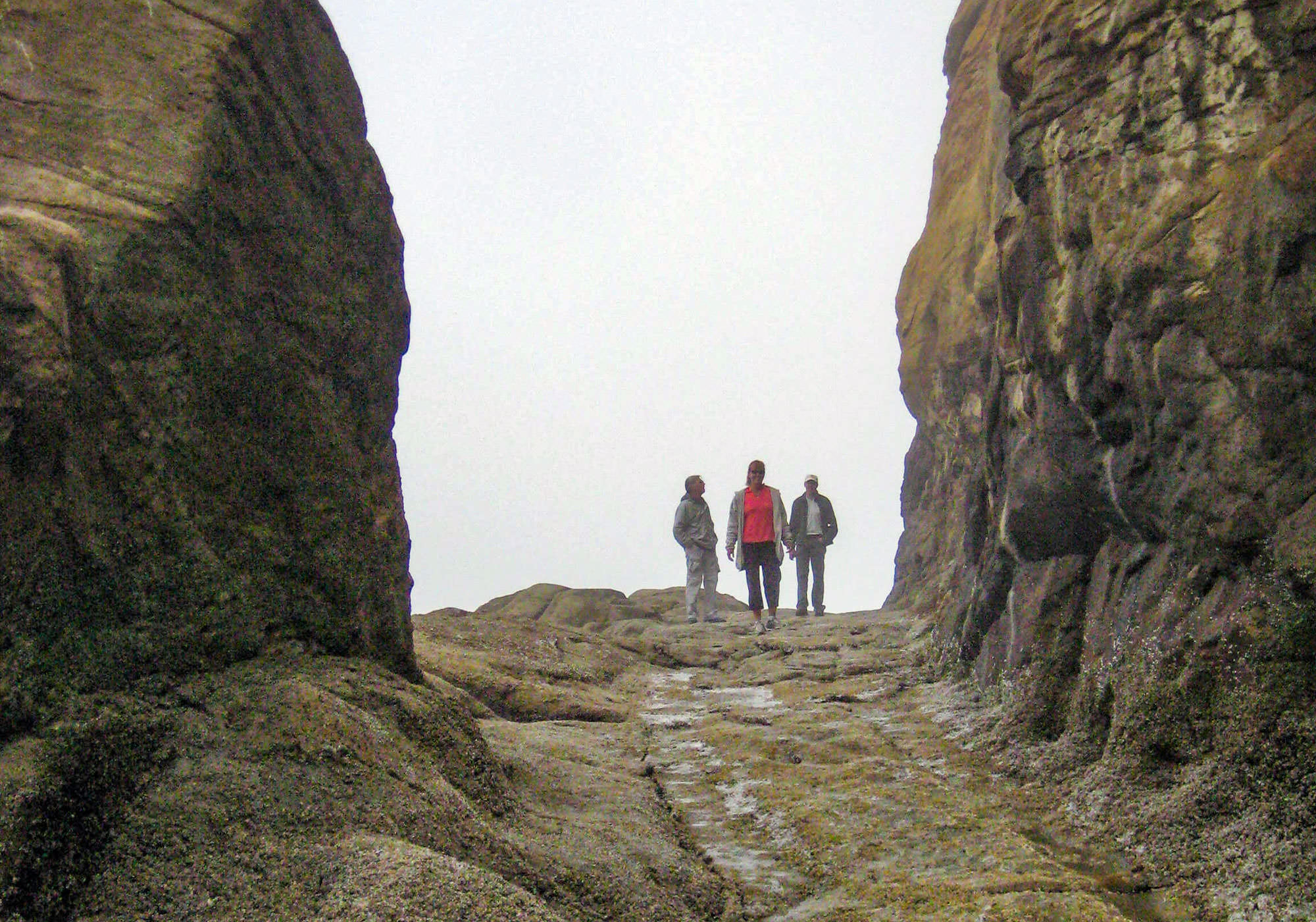 Three people stand on the former stagecoach road carved into rock.