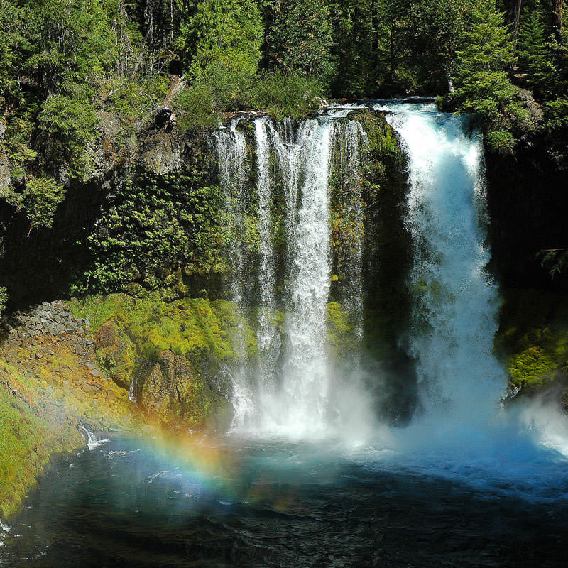 A rainbow reflects in the cascade of a large waterfall.