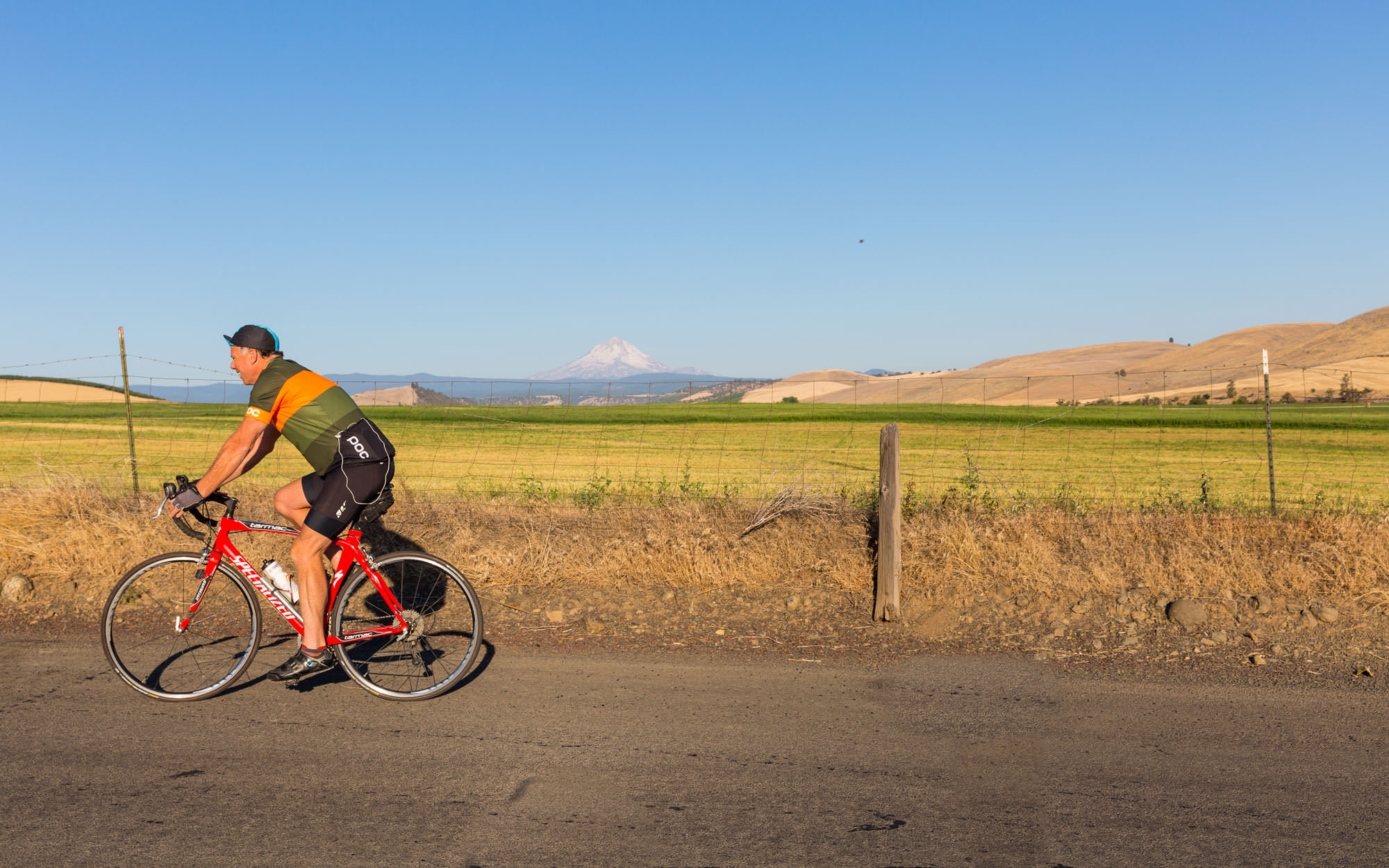 A cyclist pedals on a gravel road with a backdrop of farmland and a snow-capped mountain.