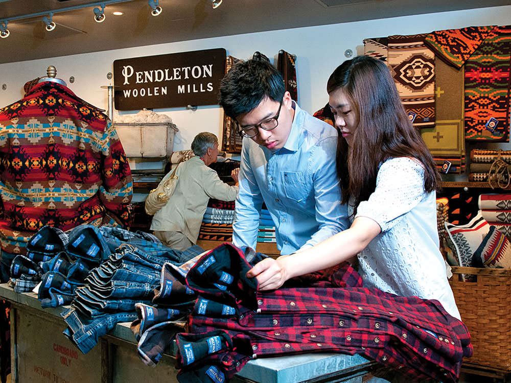 A man and woman look at plaid Pendleton shirts.