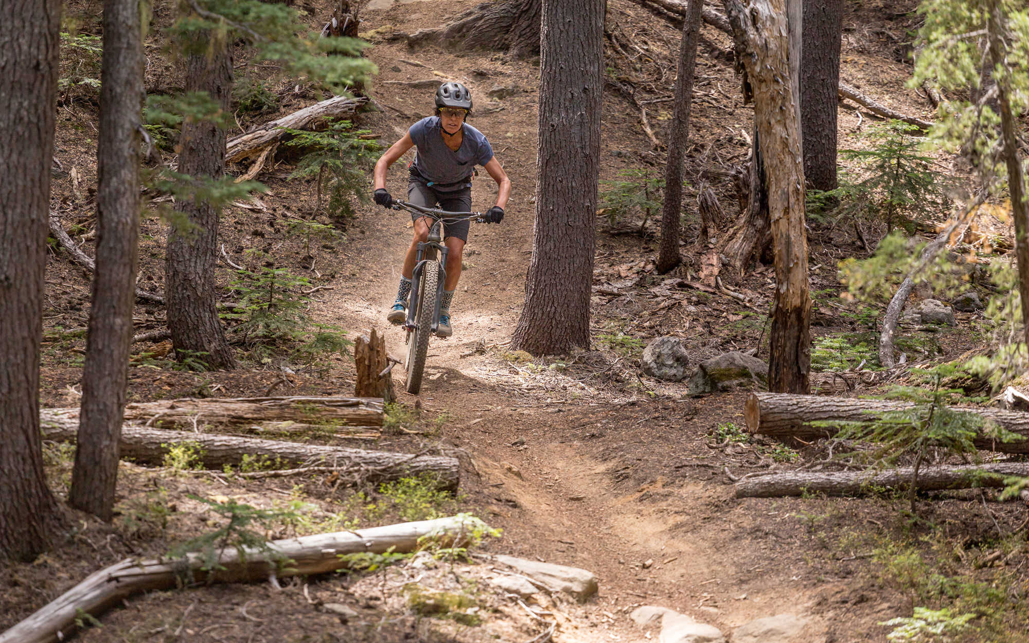 A female mountain biker pedals down a dusty forest trail.