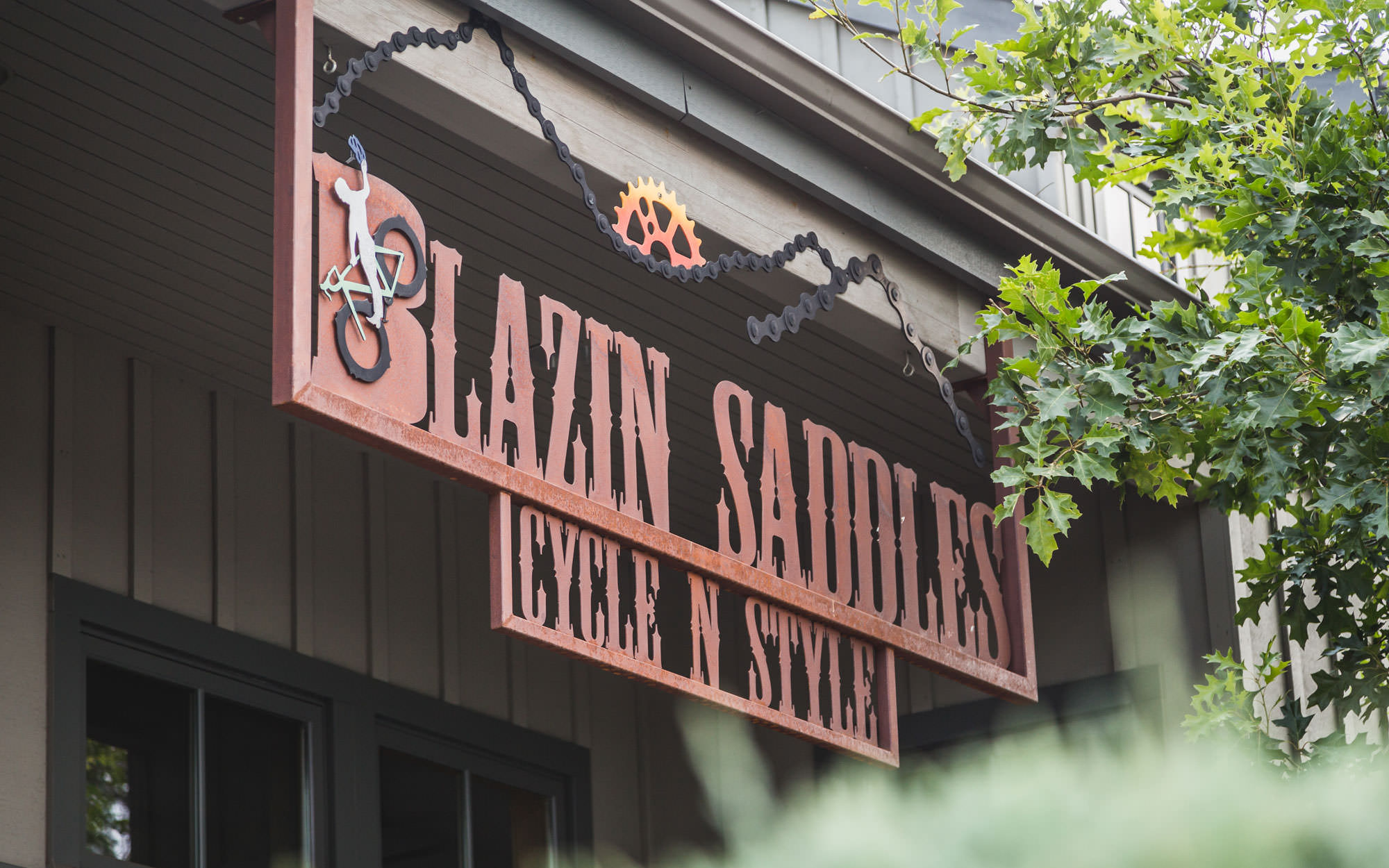 The sign of Blazin Saddles bike shop is made of bike chains and metal.