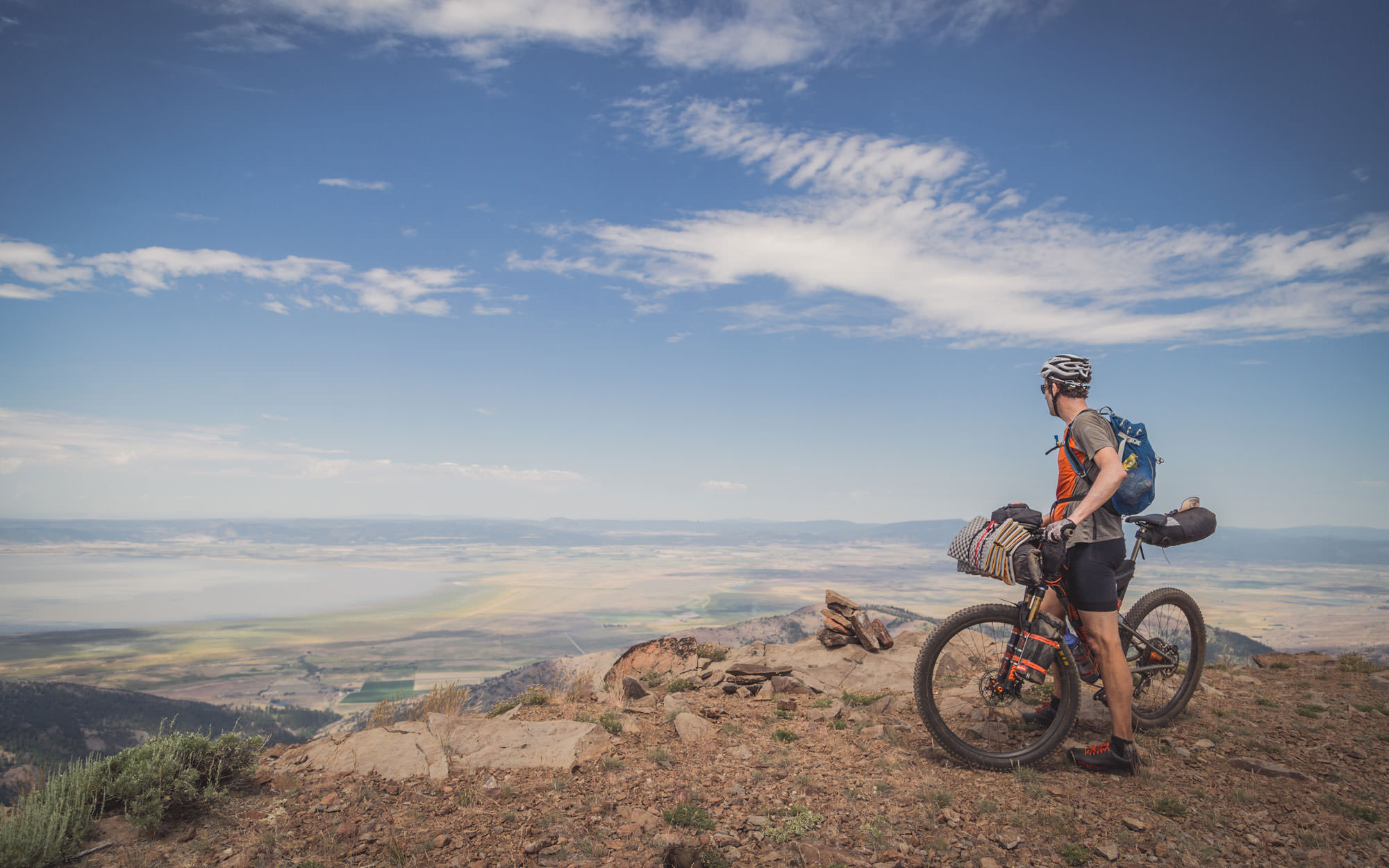 A mountain biker looks over the clouds above a valley.