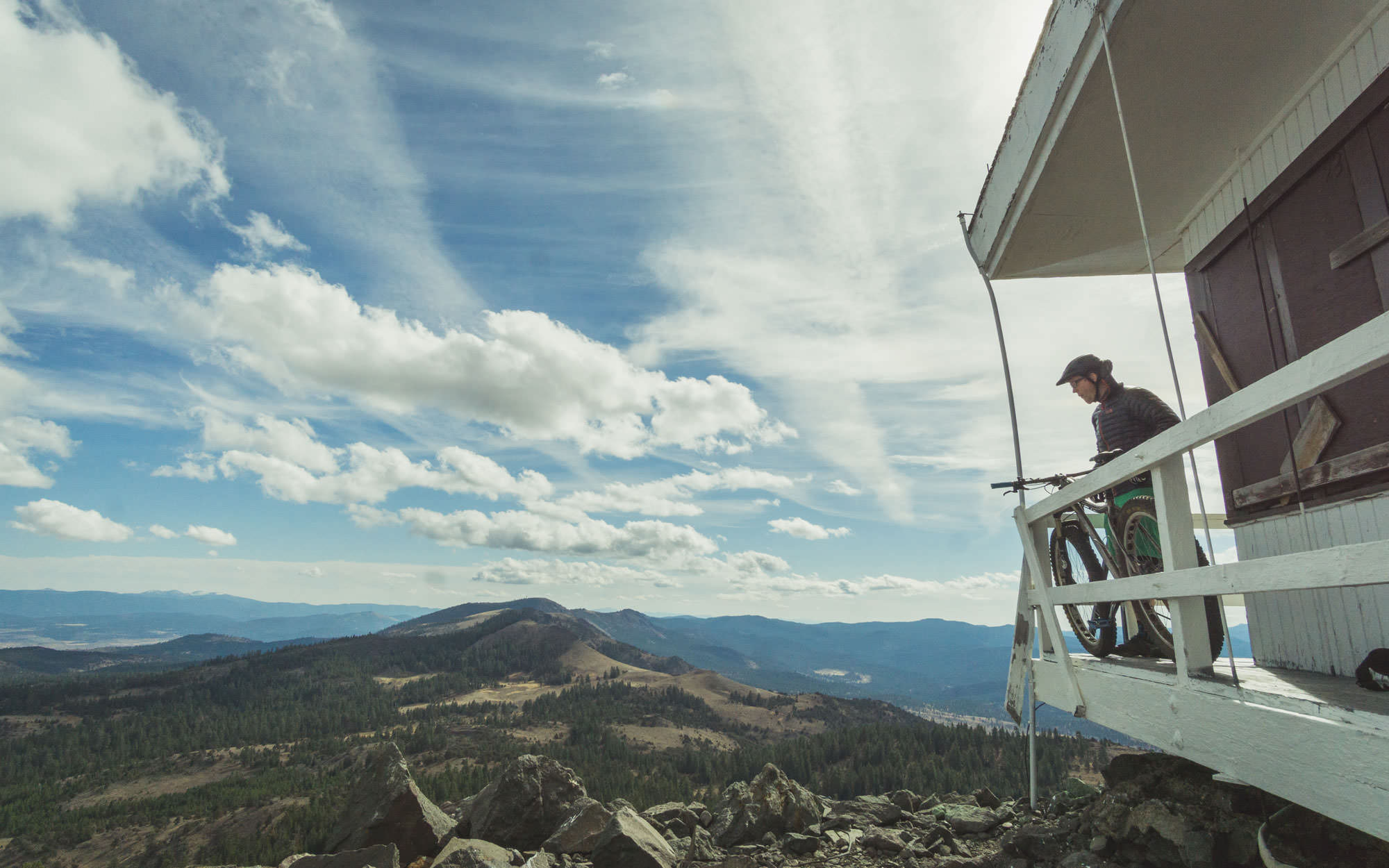 A mountain biker stands on the balcony of a fire lookout tower, looking over a vast landscape.
