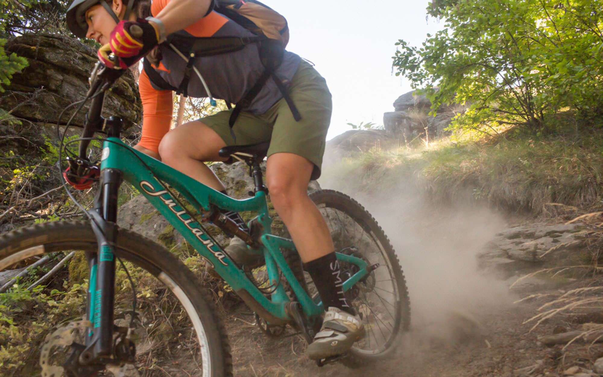 A close-up image of a mountain biker speeding down a dusty singletrack trail.