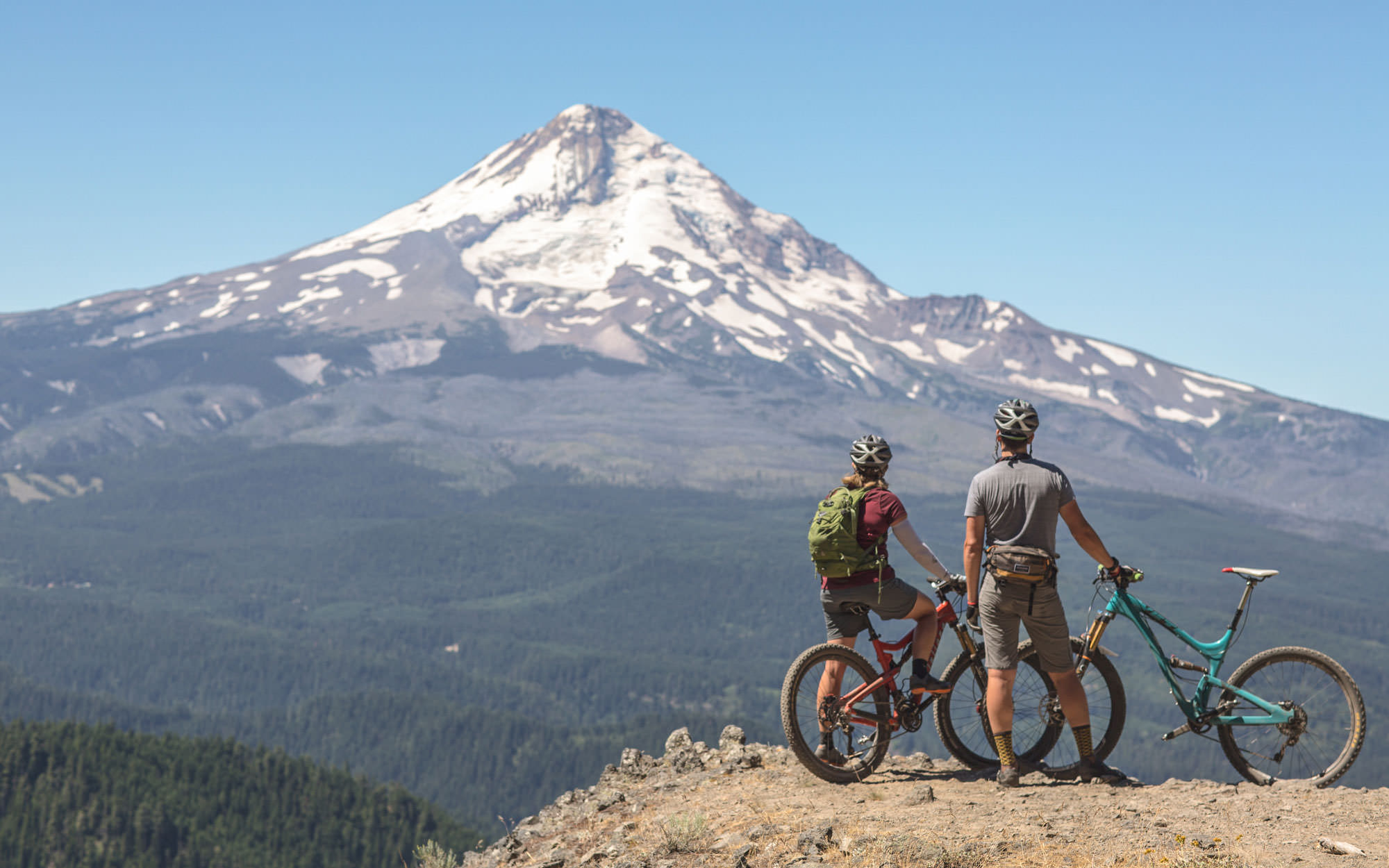 Two mountain bikers pause to look at the massive peak of Mt. Hood.