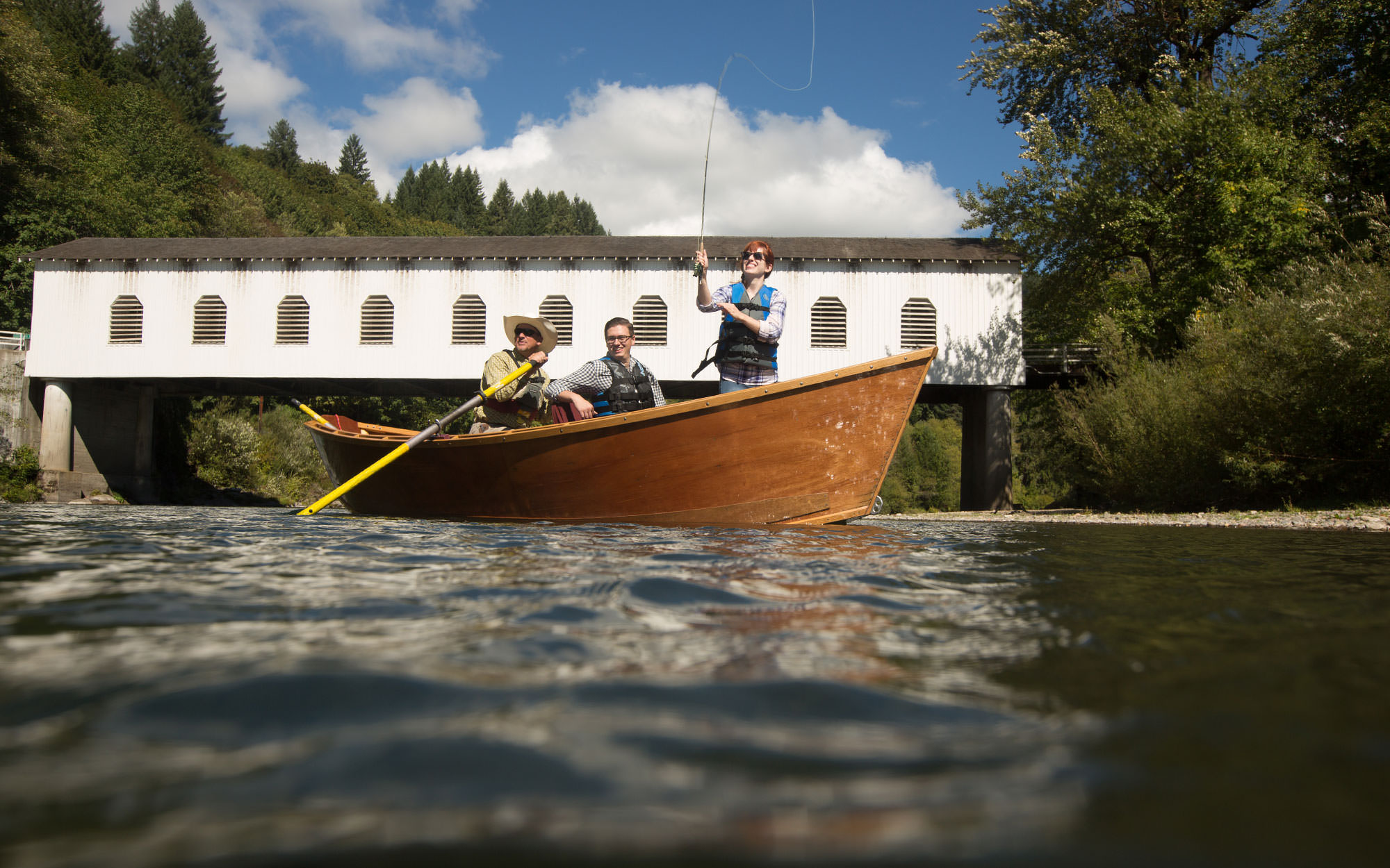 A women casts a line from a drift boat in front of a historic covered bridge.