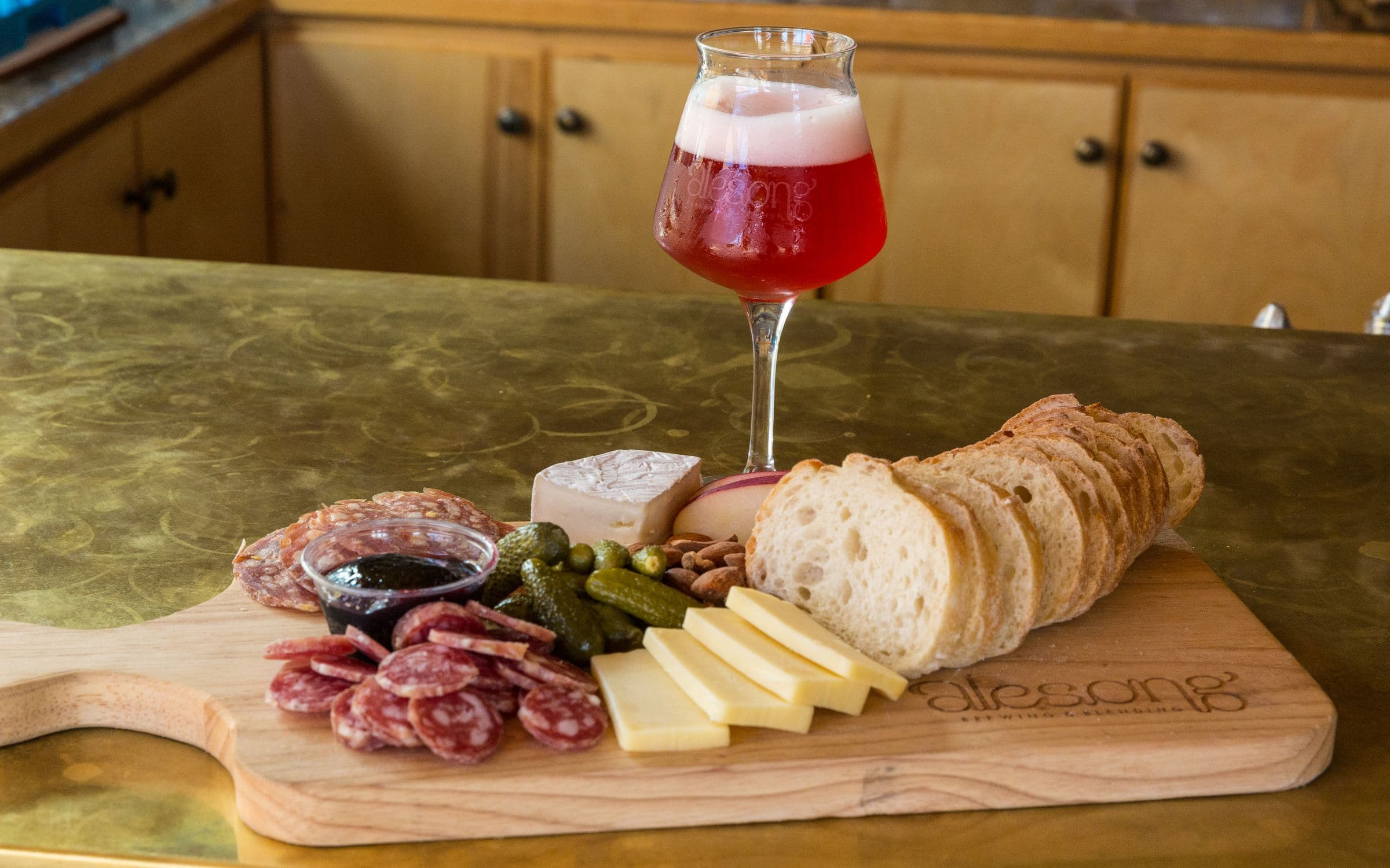 Charcuterie board and stemmed glass of barrel-aged beer.