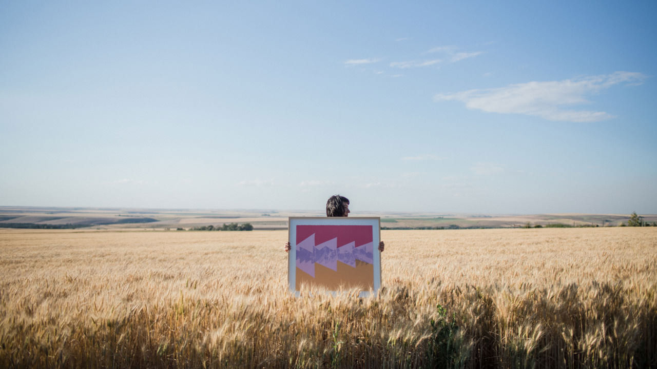Person in a wheat field holding a brightly colored work of art and blue sky above.