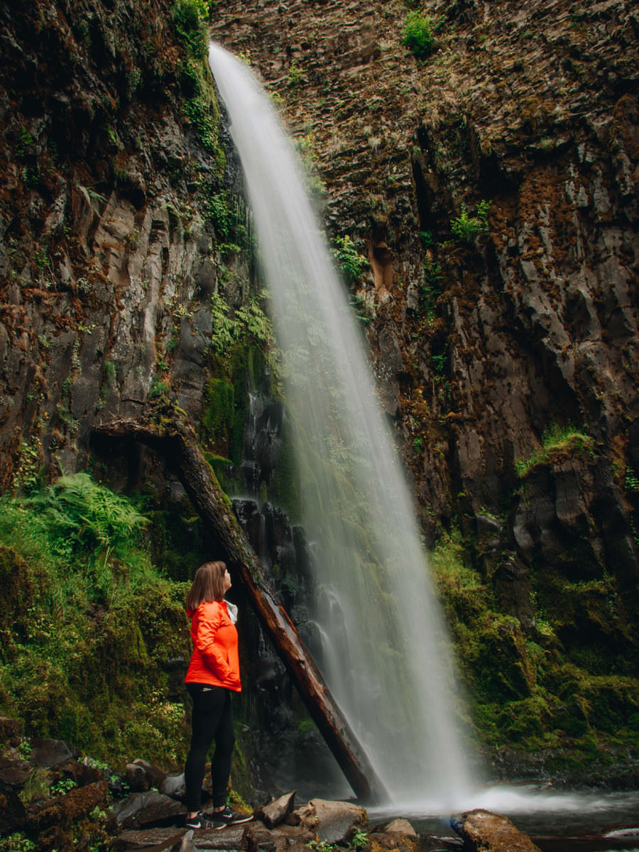 A girl in a red jacket stands next to a waterfall in awe.