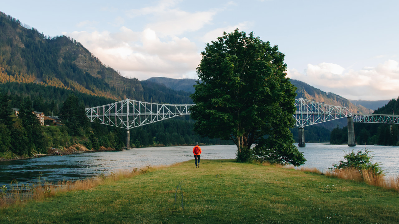 A girl in a red jacket stands at the end of a island in the middle of the Columbia River, with the metal Bridge of the Gods in the backdrop.