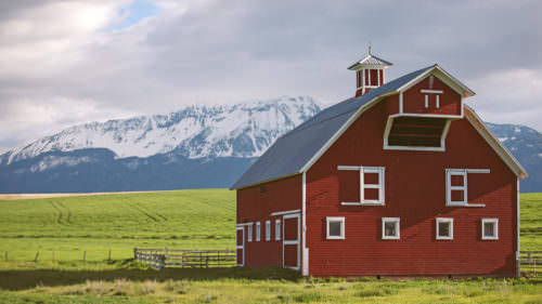 With snow-capped Wallowa Mountains in the distance, the Wallowa Barn Tour takes you on a trip through the area's fascinating history. (Photo credit: Elena Pressprich)