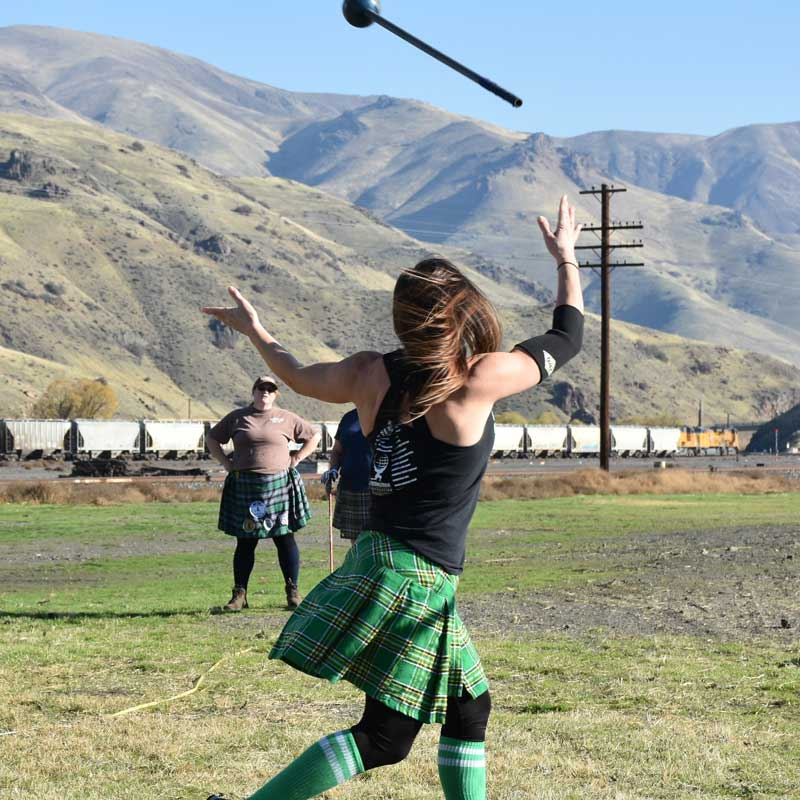 A kilt-wearing person throws a heavy ball at the highland games.